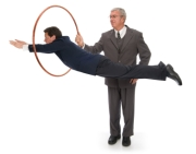 CEO holding up a hoop for his employee / client / vendor to jump through